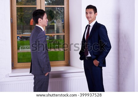 Young men international students dressed is elegant suit are talking about something, while are standing in hallway university. Skilled two male entrepreneurs having conversation during work break - stock photo