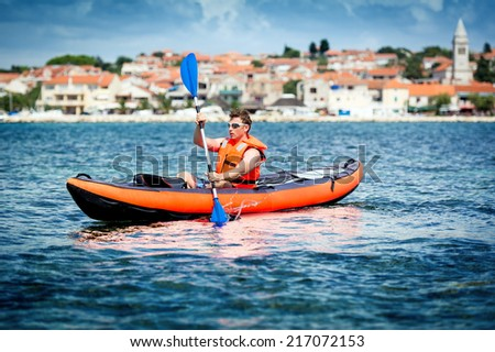 Young men paddle a kayak on the sea