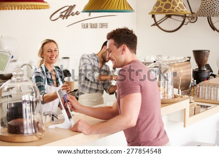 Young men paying for order in a cafe - stock photo