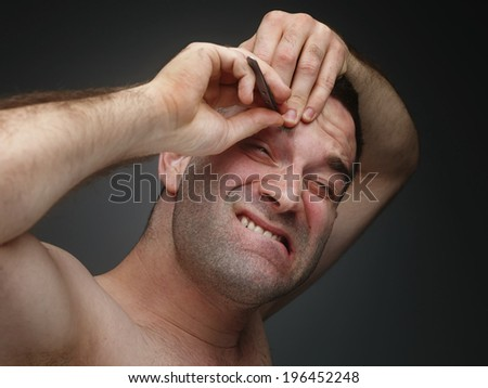 Young men pluck his eyebrows. - stock photo