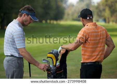 Young men standing in golf course by golf bag full of sticks - stock photo