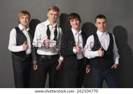 Young men standing over black background gesturing thumbs up - stock photo