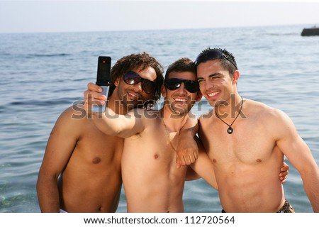 Young men taking pictures at the beach - stock photo