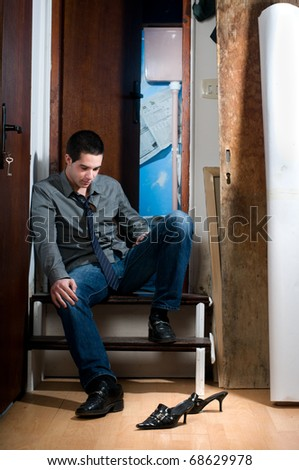 Young men thinking looking at female shoes, sitting on step in front of public toilet