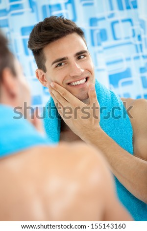 Young men touching his soft cheek after shaving - stock photo