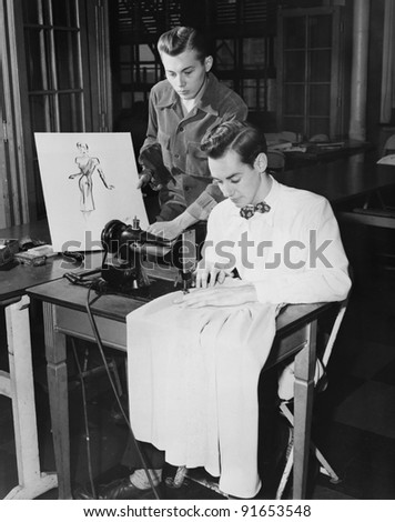 Young men using sewing machine - stock photo