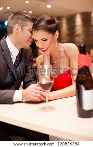 young men whispers to his girlfriend, couple in love - stock photo