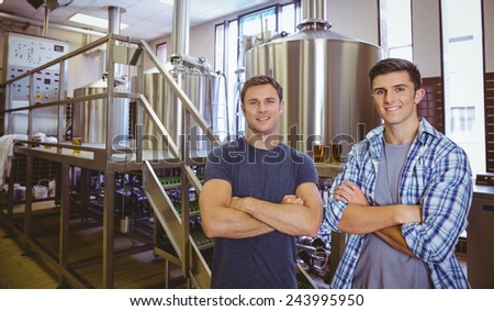 Young men with arms crossed smiling at camera in the factory - stock photo