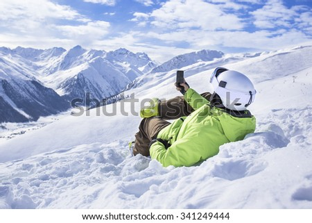 Young men with smartphone mountain winter resort - stock photo