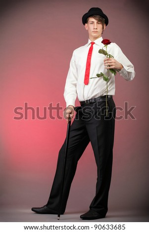Young men with the red rose on colour background. Love and reflection.