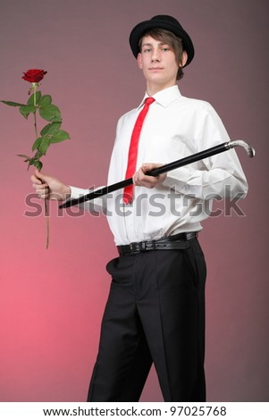 Young men with the red rose on colour background. Love and reflection. - stock photo
