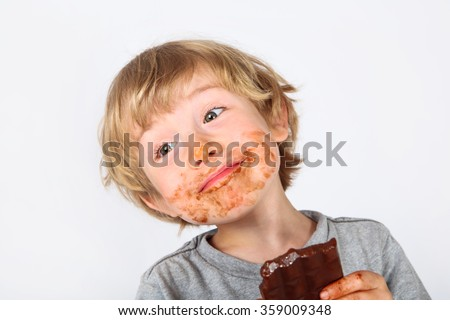 Young messy boy eating a chocolate bar with chocolate on his face on a gray background