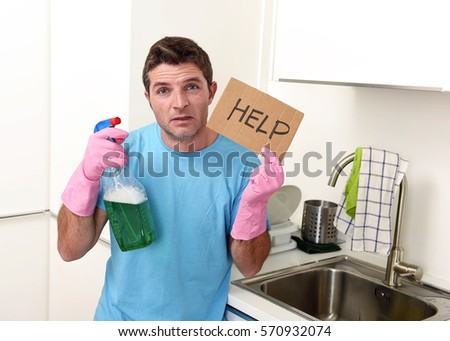 young messy man in stress in washing rubber gloves holding detergent spray bottle asking for help desperate with crazy face expression in domestic home cleaning and housework concept