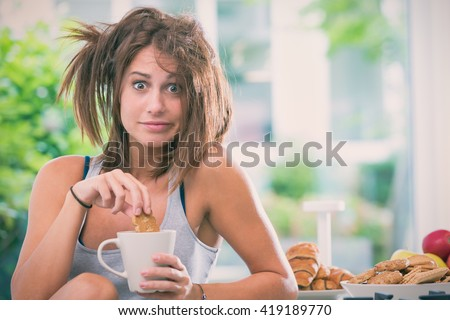 Young messy woman have breakfast in the kitchen - stock photo