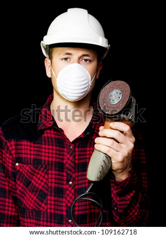 Young metal fabrication workman in a hardhat and mask holding up a small handheld rotary disc sander on a black studio background - stock photo