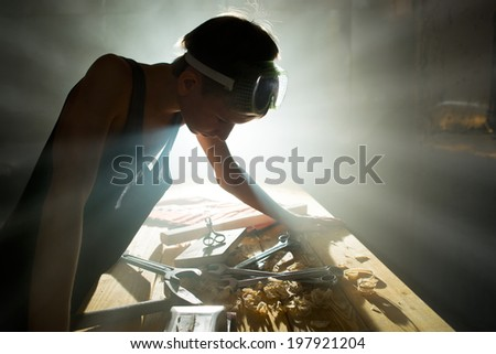 Young metalworker at work in the workshop - stock photo