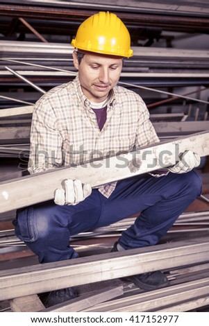young metalworker controls some metal bars in steel mill