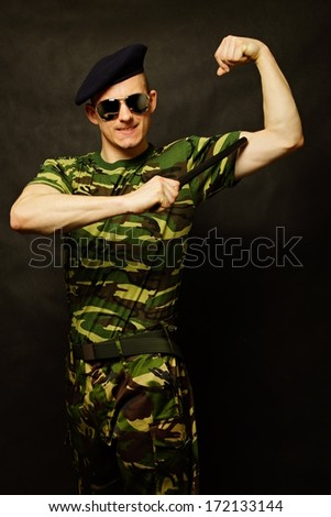 Young military man with nighstick shows biceps