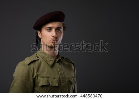 young military with red beret and green uniform on gray background