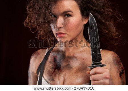Young military woman posing with knife. Ready to fight. With dirty face, wound and blood. - stock photo