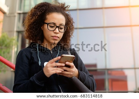 Young millenial girl texting on her mobile phone