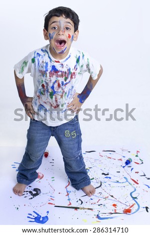 Young mischievous boy shouting with paint all over him against white background - stock photo