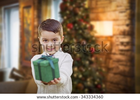 Young Mixed Race Boy Handing Gift Out Front with Christmas Tree Behind. - stock photo