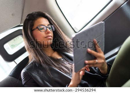 Young mixed race businesswoman portrait inside a taxi in Canary Wharf area in London while using a tablet. - stock photo