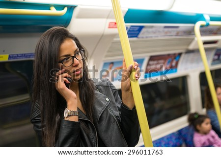 Young mixed race businesswoman portrait inside underground wagon in London talking at the phone.
