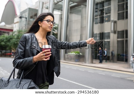 Young mixed race businesswoman portrait looking for a taxi outdoors in Canary Wharf area in London with modern building as background.  - stock photo