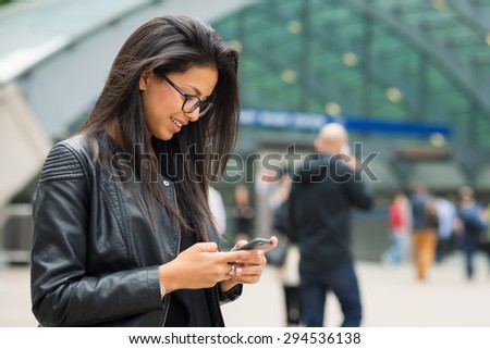 Young mixed race businesswoman portrait outdoors in Canary Wharf area in London with modern building as background while using smartphone. - stock photo