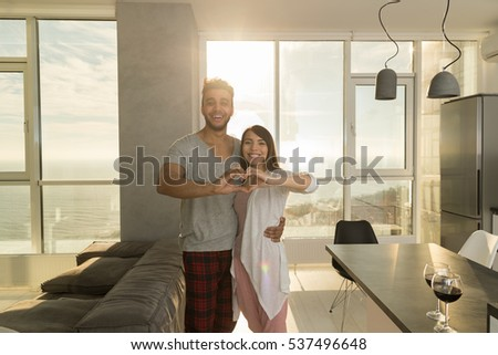 Young Mixed Race Couple Apartment Panoramic Window Sea View Morning, Happy Hispanic Man Asian Woman Embracing Making Heart Shape Modern Kitchen