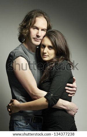Young mixed race couple looking sad and thoughtful cuddling on plain background
