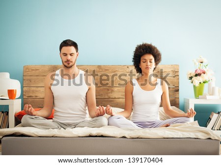 Young mixed-race couple meditating together in their bedroom. - stock photo