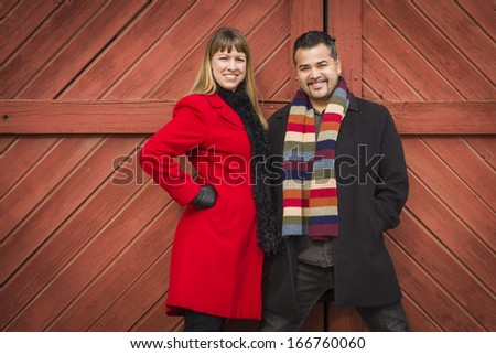 Young Mixed Race Couple Portrait in Winter Clothing Against Barn Door. - stock photo