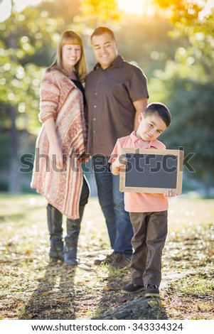 Young Mixed Race Couple Stands Behind Son with Blank Chalk Board Outdoors. - stock photo