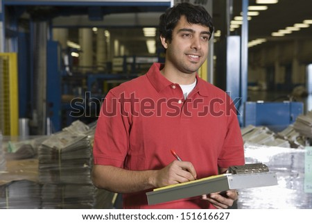 Young mixed race man working in the newspaper factory