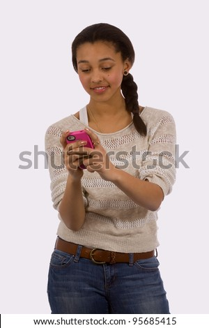 Young mixed race mulatto teen age girl wearing jeans looking at her cell phone text messaging