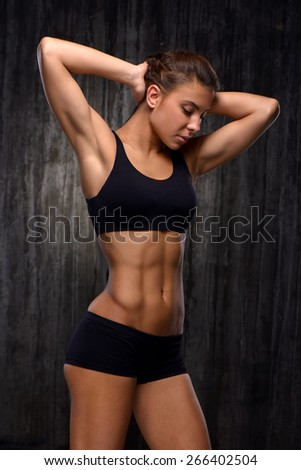 Young mixed race sporty woman wearing black tracksuit for training. She demonstrating her biceps and slim figure. Fitness concept - stock photo
