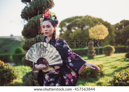 Young model Beautiful Japanese Chinese woman in kimono national posing in the park garden, spring summer, Asia, in the rays of the setting sun, graceful - stock photo
