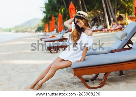Young model girl,posing on the beach front,near resort. Smiling and having.Enjoy her vocation.Wear white dress and beautiful retro hat.Natural beauty. - stock photo