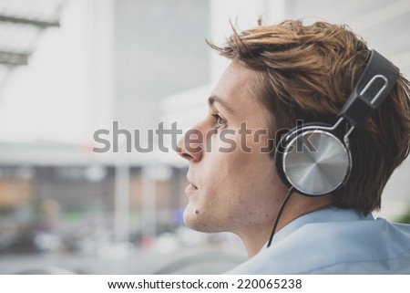 young model handsome blonde man with headphones in the city - stock photo