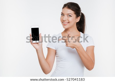 Young model in t-shirt showing at phone in studio. Isolated white background