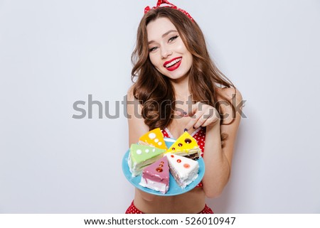 Young model in underwear shows finger on cake. isolated gray background