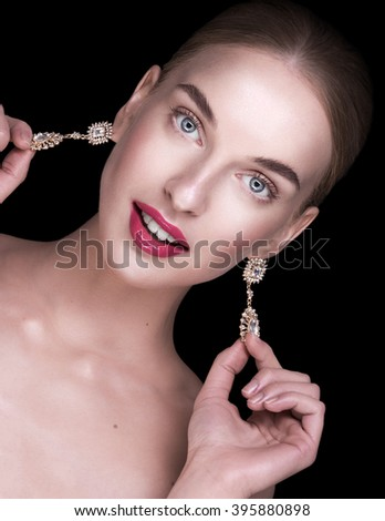 young model looking into the camera, shows precious earrings, grins - stock photo