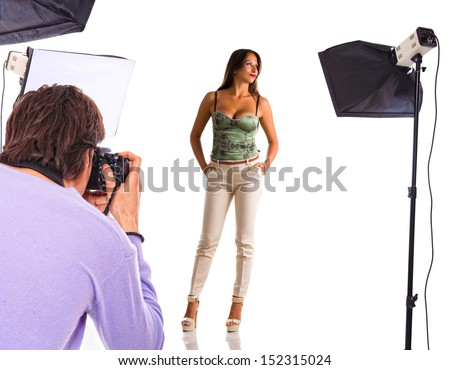 Young model poses for young photographer in photo studio - stock photo