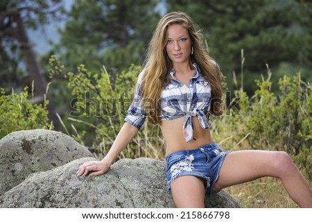 Young model posing and sitting on the rocks in blue flannel shirt and denim shorts - stock photo