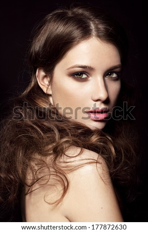 Young model with big lips and make up, brunette, black background Fashion look