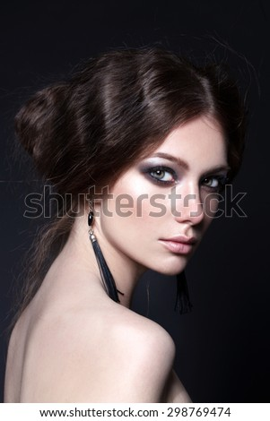 Young model with big lips and make up, smoky eyes, brunette, black background Fashion look. Jewelry. - stock photo