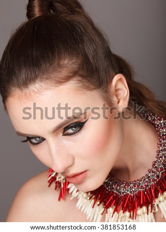 Young model with big lips and make up, smoky eyes, brunette, grey background. Fashion look. Jewelry.